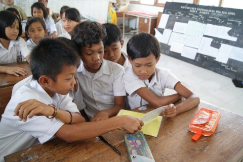 SD Sumber students reading a postcard from Australia