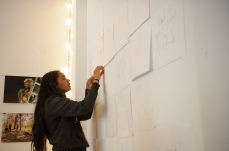 A participant adds her drawings to the exhibition at the You Are Here Hubspace.